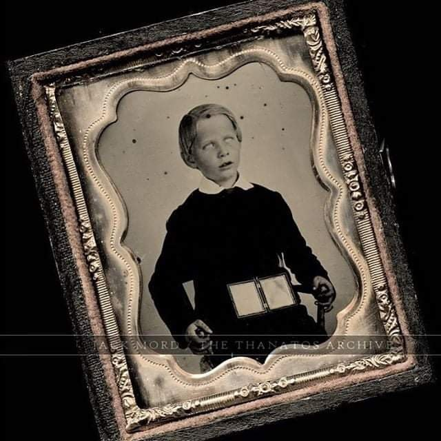 Creepy memorial photo of a boy with open daguerreotypes in his lap. This is not a post mortem photo.